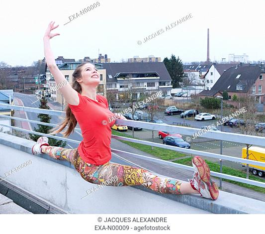 woman exercises urban yoga outdoor on a terrace with the city in the background