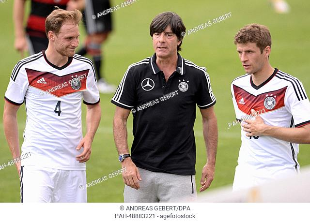 Head coach Joachim Loew (C) talks to Benedikt Hoewedes (L) and Thomas Mueller of the German national soccer team during a break of a friendly soccer match...