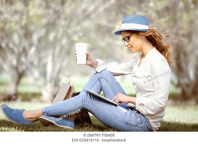Happy young woman a disposable coffee cup sitting on the grass and using touch pad on her tablet in a summer park