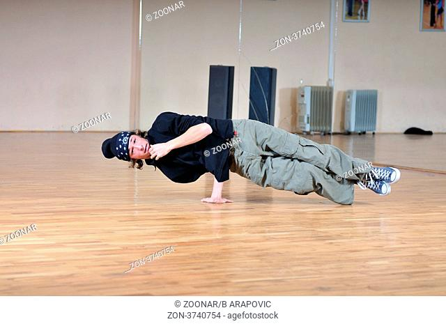 young man performing break dance in dance studio