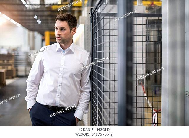 Businessman standing in factory shop floor thinking