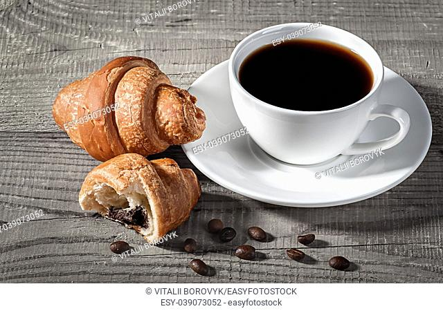 Coffee and croissants on a wooden table. Broken croissant and coffee beans nearby