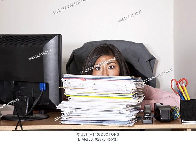 Japanese businesswoman hiding behind stack of papers