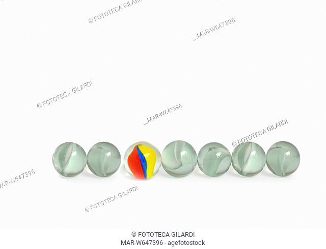BIGLIE un biglia multicolori in mezzo a sei biglie in vetro bianche. , 2008,,Copyright © Fototeca Gilardi