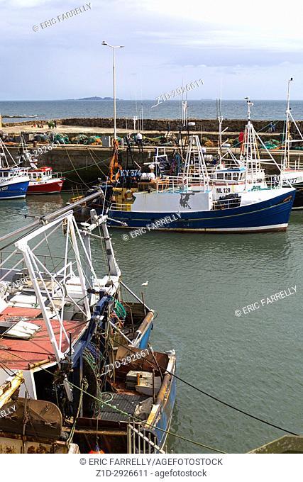 Fishing boats alongside Pittenweem harbour. Fife Scotland UK