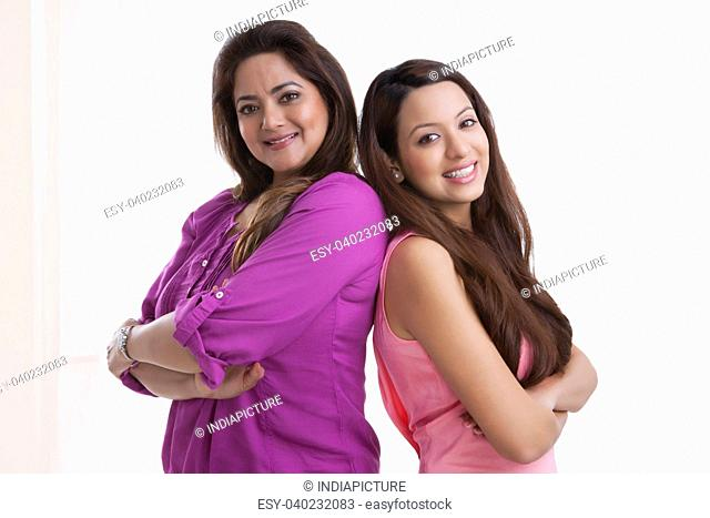 Portrait of mother and daughter standing back to back