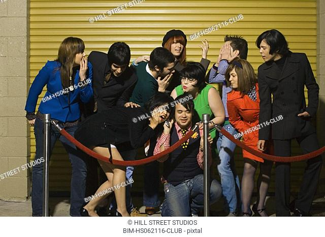 Group of young adults behind velvet rope