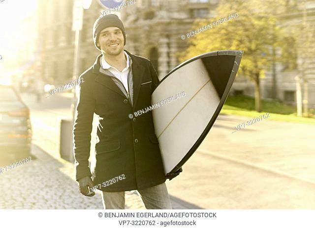 man with surfboard on street, in Munich, Germany