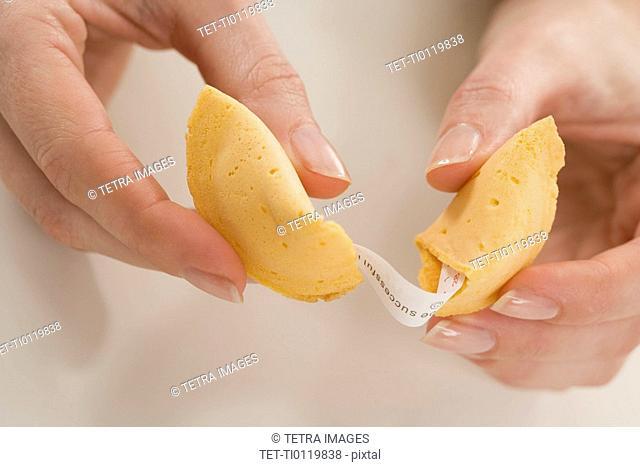 Woman breaking fortune cookie