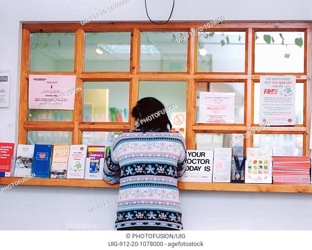 Female patient at GP surgery reception desk, Berkshire UK