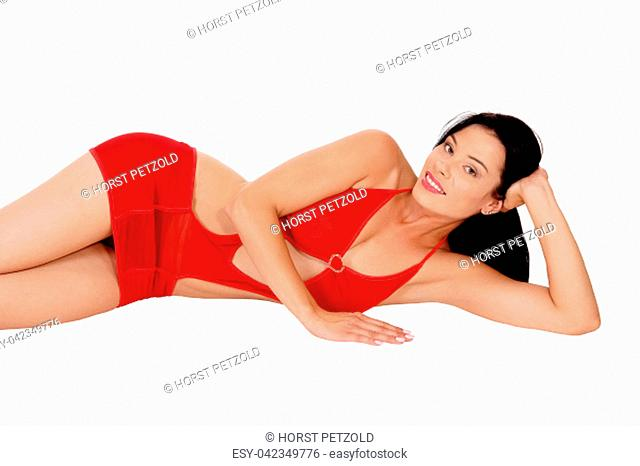 A beautiful slim young woman lying in red lingerie on the floor with.her long black hair, smiling, isolated for white background