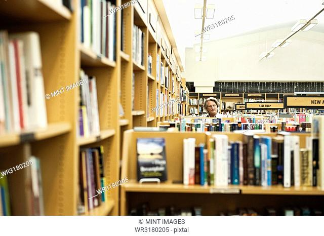 Caucasian male browsing through books in a large bookstore