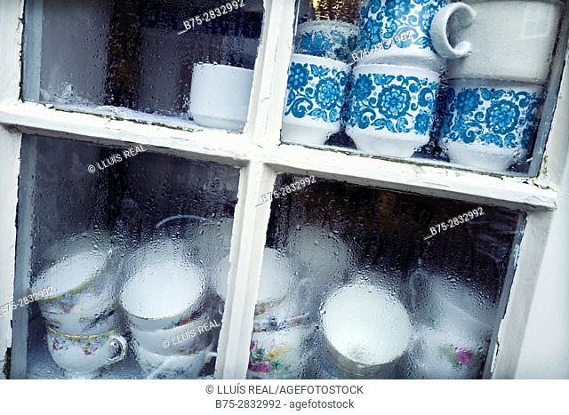 Close-up of a window with a shelf full of teacups. Harrogate, North Yorkshire, England, UK