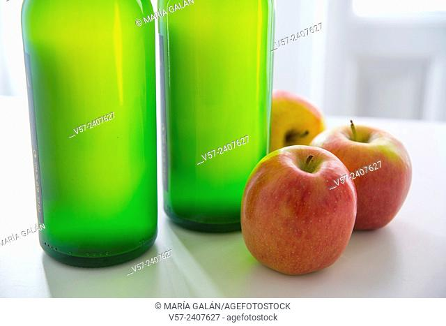 Two bottles of cider and three apples. Close view