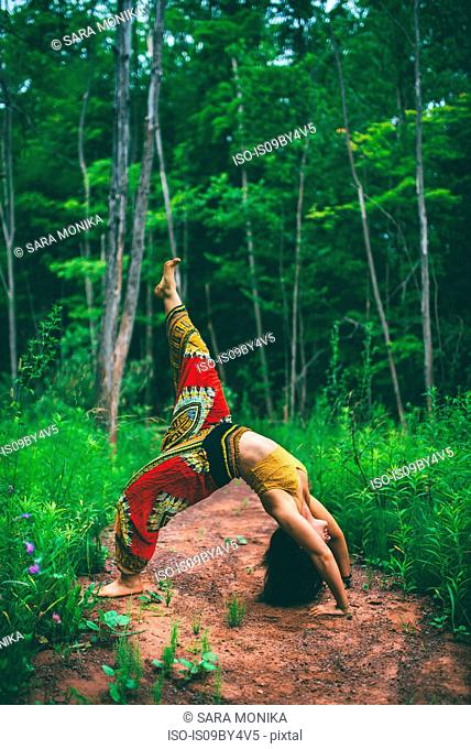Woman doing backbend pose in forest