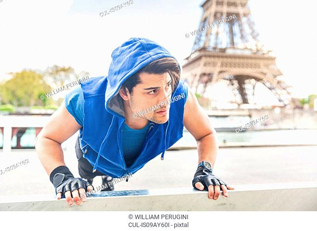 Young man exercising outdoors, doing pushups, Eiffel Tower in background