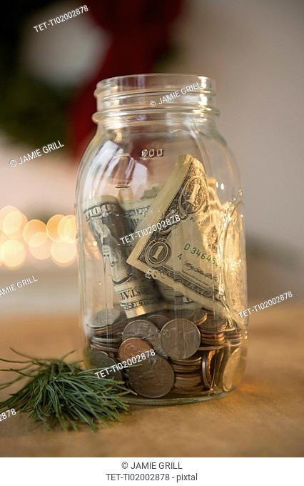 Jar with dollar bills and coins