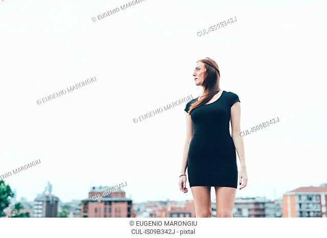 Young woman in mini dress looking over her shoulder above city