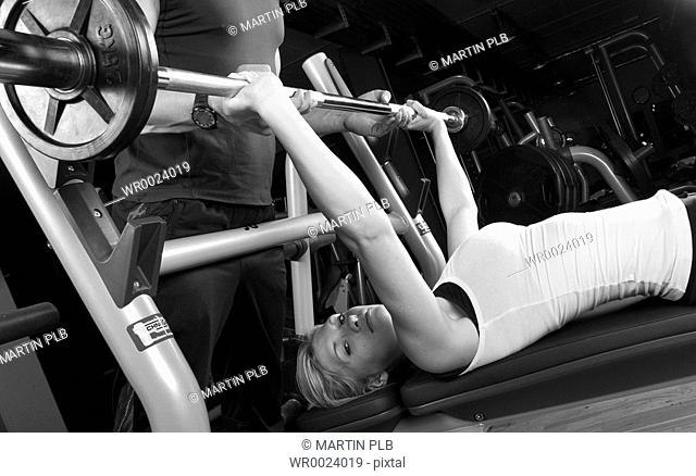 young woman doing strength training in fitness studio, instructed by trainer