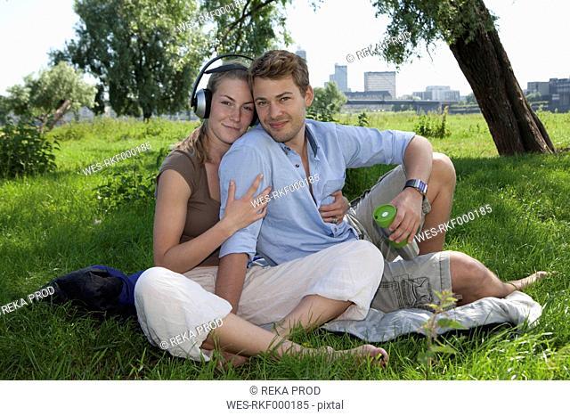 Germany, North Rhine Westphalia, Duesseldorf, Couple sitting on grass and listening music, smiling, portrait