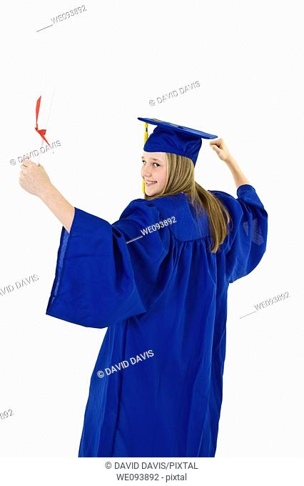 A preteen caucasian girl with blond hair standing in blue graduation gown and smiling  She is on a white background