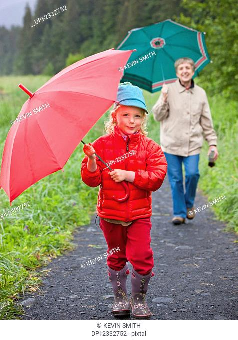 Grandmother and granddaughter playing with their umbrella while walking up the path from the beach at Lowell Point on a rainy day, summer, Seward