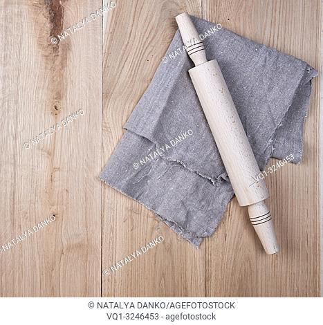 wooden rolling pin and a gray textile towel on a brown wooden table, copy space