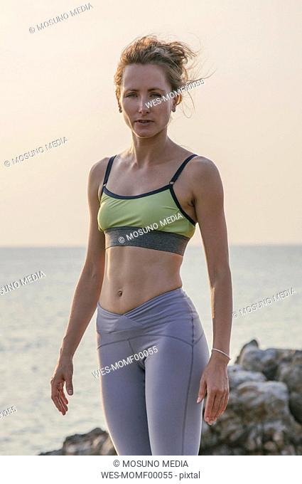Woman in fitness clothing standing by the sea