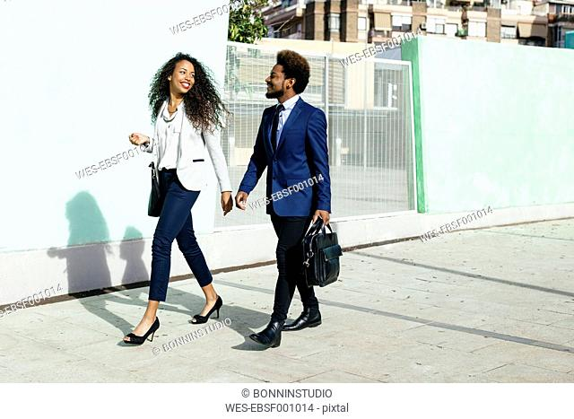 Smiling young couple wearing business clothing walking hand in hand on pavement