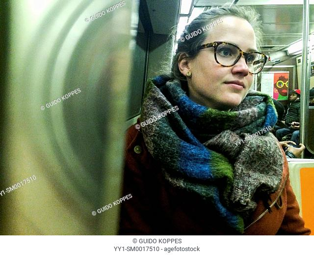 New York City, USA. Young, brunette woman commuting by subway