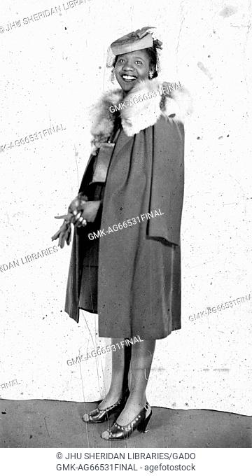 Full length standing portrait of a a young African American woman holding a pair of dark gloves, wearing a dark overcoat with fur collar, jewelry, and hat