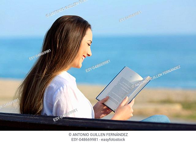 Happy woman reading a paper book sitting on a bench on the beach