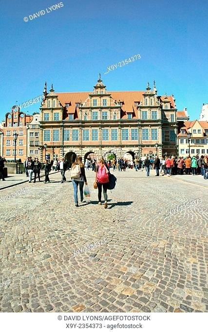 Gdansk Poland. Tourists walk across the Zielony Bridge to the 16th C Renaissance period Green Gate entrance to the Old Town