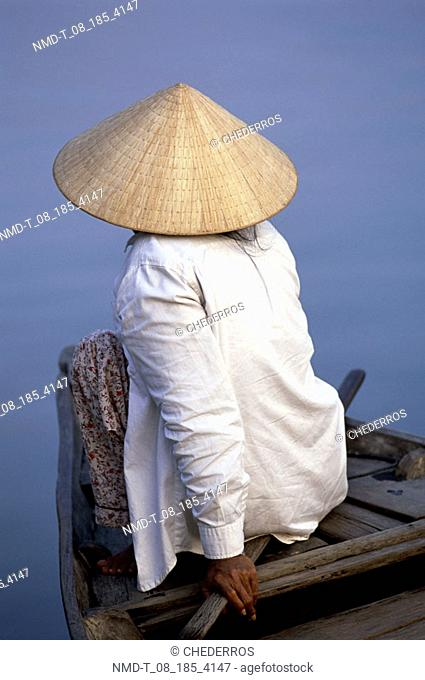 Rear view of a man sitting in a boat, Vietnam