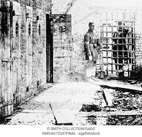 A photograph of the exterior of a slave pen, the pens themselves consist of narrow wooden doors with small holes to allow light in to the cramped rooms