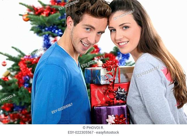 Excited young couple stood by the Christmas tree