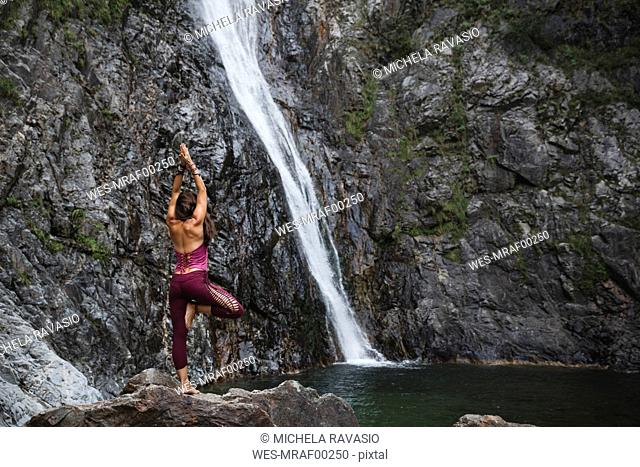 Italy, Lecco, woman doing Tree Yoga Pose on a rock near a waterfall