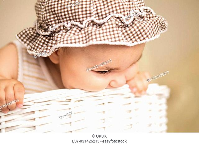 Eight month baby girl play with laundry basket