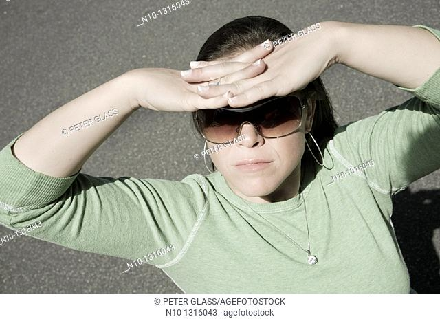 Young woman, wearing sunglasses, blocking the sun with her hands