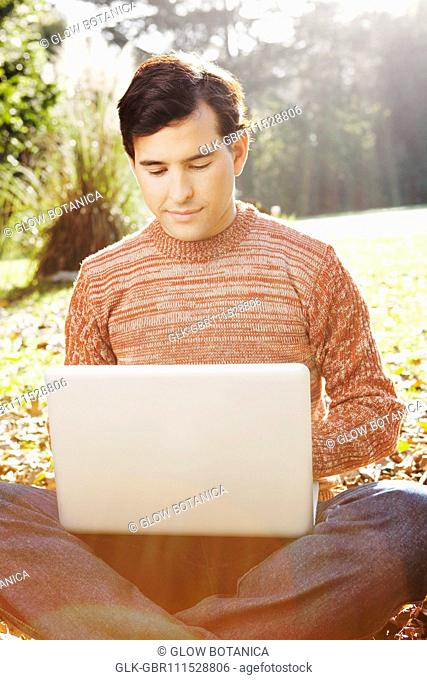 Man sitting on leaves using a laptop