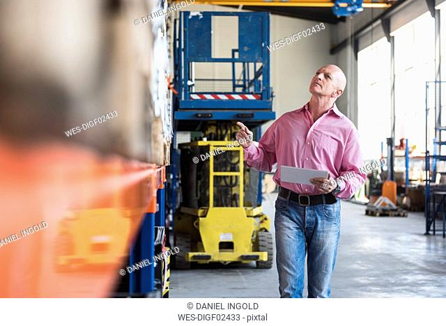Man with tablet walking in industrial hall looking at shelves