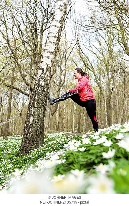Woman stretching in spring forest