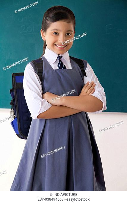 Portrait of girl smiling with her arms crossed standing in front of a blackboard in a classroom