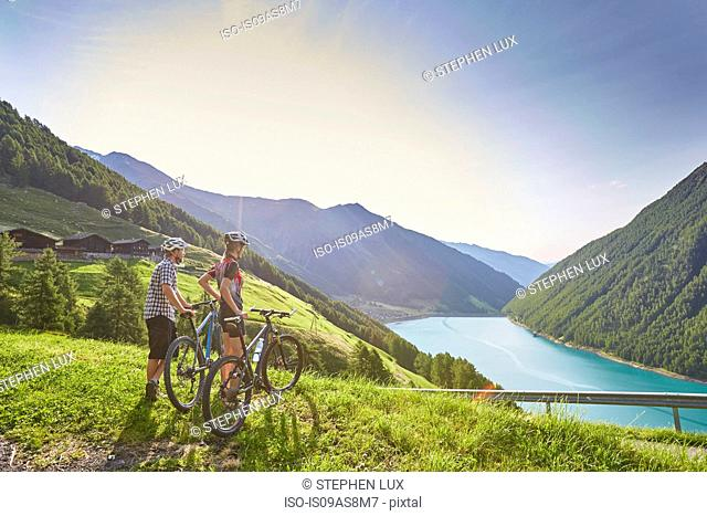 Young mountain biking couple looking out over Vernagt reservoir and Finailhof farmhouse, Val Senales, South Tyrol, Italy