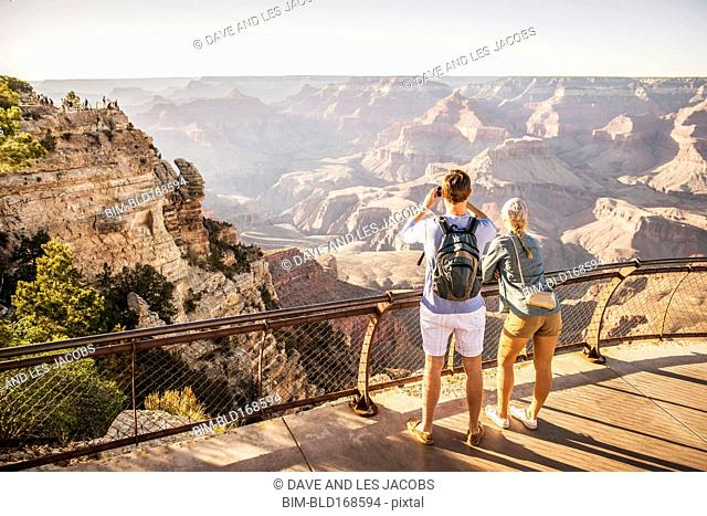 Caucasian couple photographing Grand Canyon, Arizona, United States