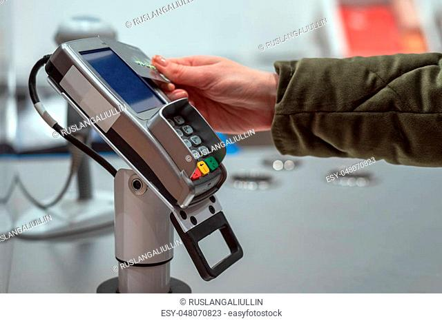 Women's hand pays for purchases in the store card contactless way, wireless technology, paypass