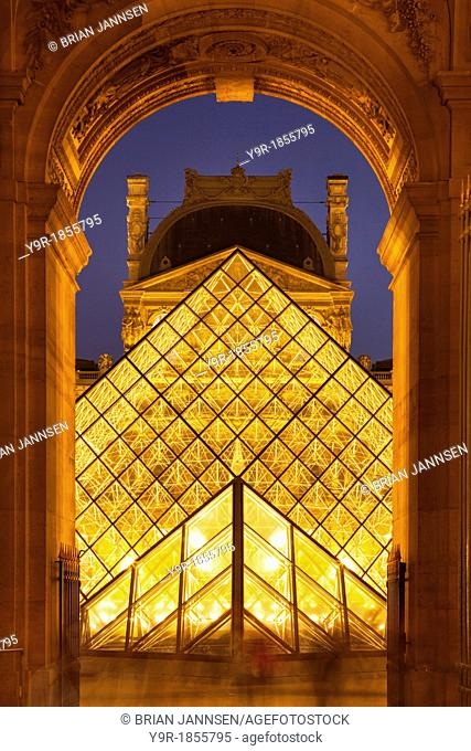 Evening at the glass pyramid at Musee du Louvre, Paris France