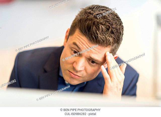 Worried businessman looking at computer in office
