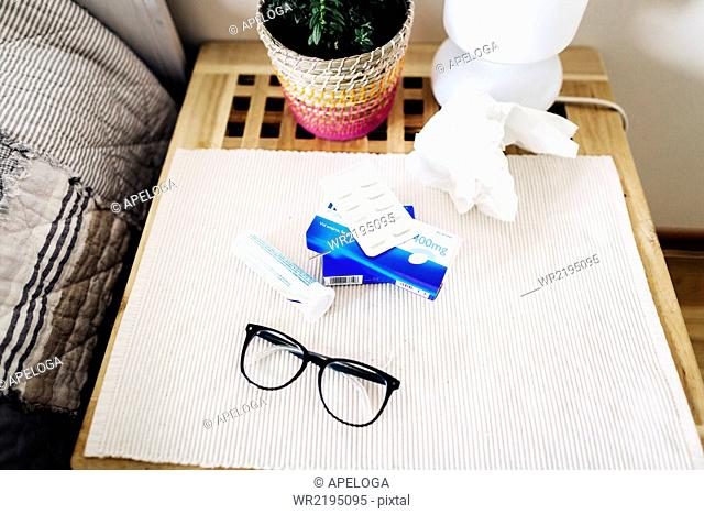 High angle view of eyeglasses and medicines on side table at home