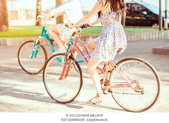 The two young girls with bicycles in park in summer